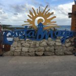 family with Costa Maya sign
