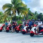 5 couples on scooters in a tropical location