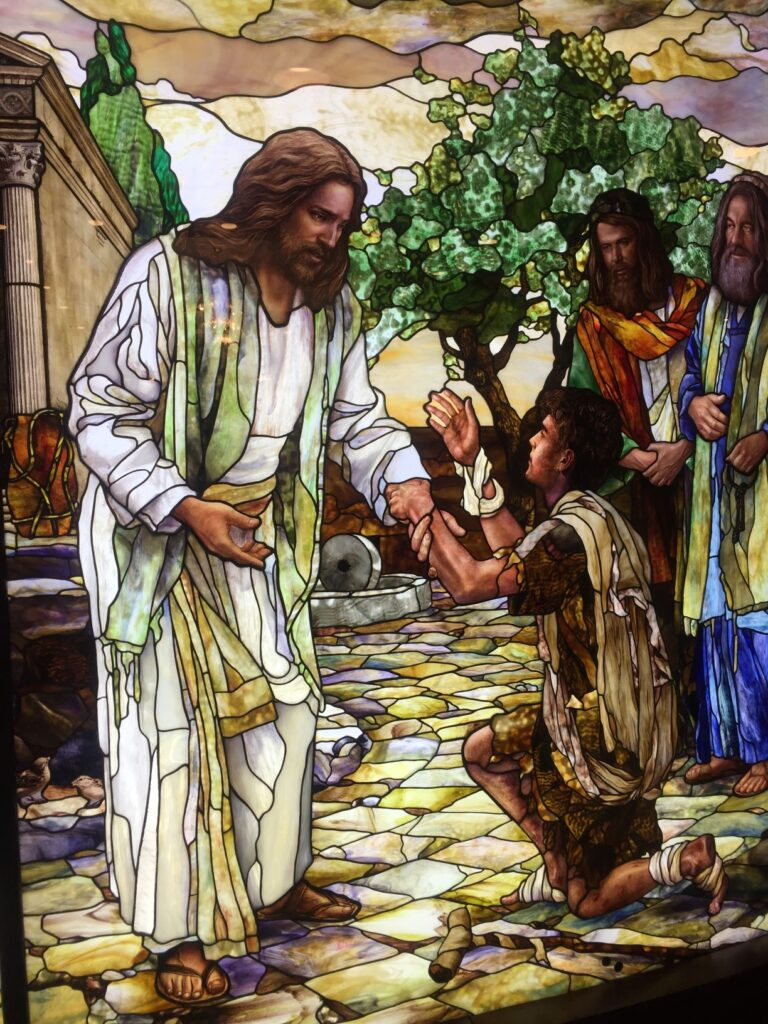 stained glass mural of Jesus Christ healing the lame man