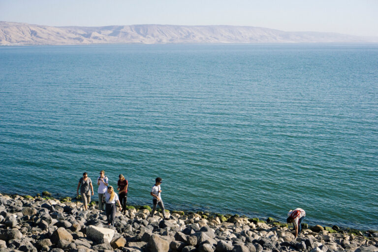 people walking on the rocky Shores of Galilee